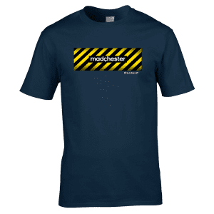 """Bespoke Manchester T-Shirt designed by artist Mark Reynolds. The T-Shirt features a hazard warning sign background with the words Madchester on. It also features the words """"Fit In Or Fac Off"""" representing the Fac in Fac 51 The Haçienda. FAC 51 was its official designation in the Factory catalogue."""